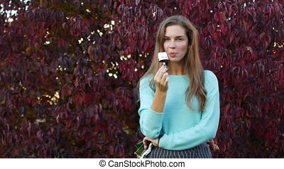 Woman Eating Ice Cream in Autumn Park