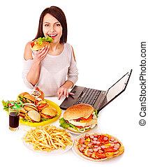 Woman eating junk food. - Woman eating fast food at work....