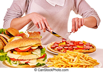 Woman eating junk food. - Body part of woman eating pizza at...