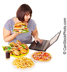 Woman eating junk food. - Woman eating fast food at work. ...