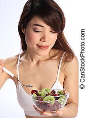 Woman eating kiwi and grapes