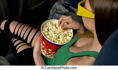 Woman eating large container of popcorn in cinema or movie theater. 3D glasses