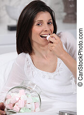Woman eating marshmallows in bed