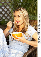 Woman eating muesli on the terrace