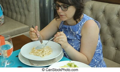 Woman eating pasta in cafe