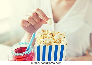woman eating popcorn with drink in glass mason jar