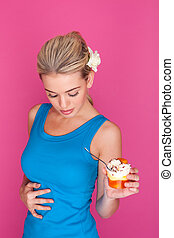 woman eating pudding looking at her belly