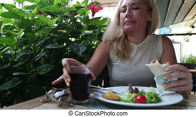 Woman eating  salad and meat