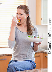 Woman eating salad in the kitchen