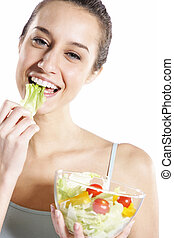 Woman eating salad. Portrait of beautiful smiling and happy woman enjoying a healthy salad and cherry tomatoes