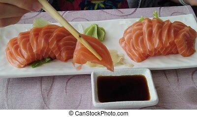 Woman eating salmon sashimi - Slow motion on glamour woman...
