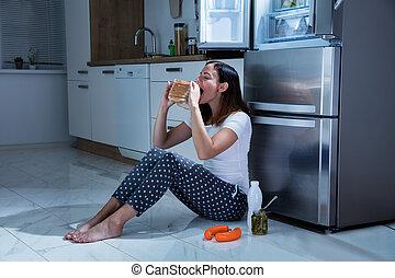 Woman Eating Sandwich In Kitchen