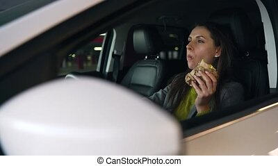Woman eating sandwich sitting in the car on the parking....