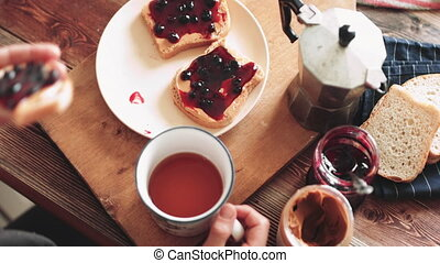 Woman eating sandwich with peanut butter and jam. - Woman...