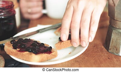 Woman eating sandwich with peanut butter and jam.