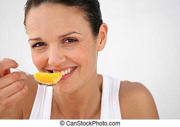 woman eating slice of orange