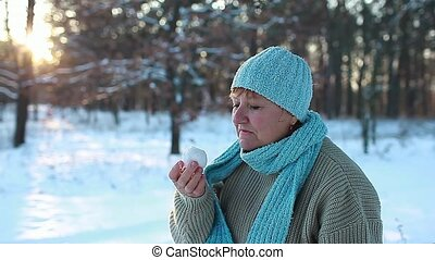 Woman eating snow in winter forest. Funny senior lady ...