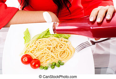 woman eating spaghetti with ketchup - hands of a woman...