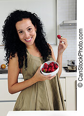 Woman eating strawberries in a modern kitchen