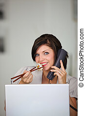 Woman eating sushi while talking on the phone