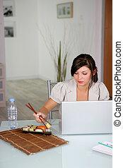 Woman eating sushi whilst using laptop