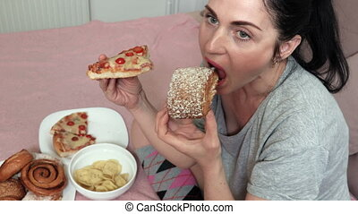 Woman eating sweet bun and piece of pizza.Bad unhealthy ...