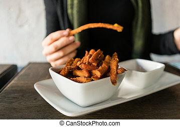 Woman eating sweet potato fries in restaurant