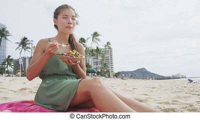 Young woman eating traditional Hawaii dish. Female in sundress is holding poke salad plate while sitting on beach. Tourist is representing her healthy lifestyle.