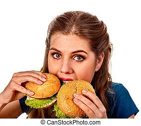 Woman eating two hamburgers. Girl bite of very big burger