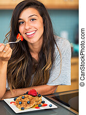 Woman eating Waffles with Fresh Fruit