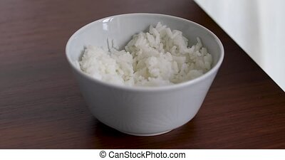 Woman eating white rice with chopsticks at home interior