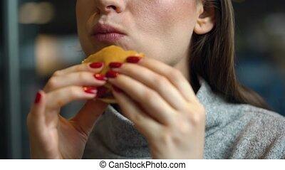 Woman eats a hamburger in a cafe - Caucasian woman eating...