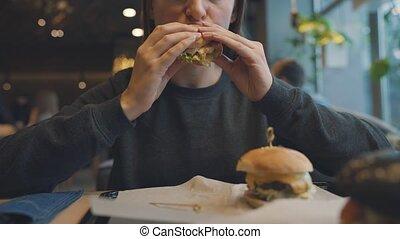 Woman eats a hamburger in a cafe
