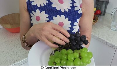 Woman eats apple cloves and grapes.Vegetarian concept