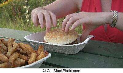 Woman eats cheeseburger. - A woman eats a delicious looking...