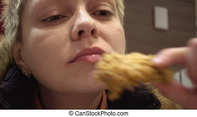 Woman eats in fastfood restaurant - Woman expressively eats...