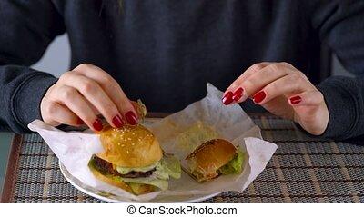 Woman eats juicy hamburger - Caucasian woman eating juicy...