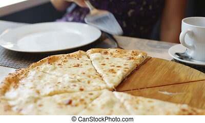 Woman eats pizza in cafe.