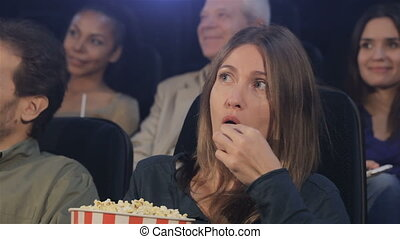 Woman eats popcorn at the movie theater - Middle aged woman ...