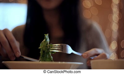 Woman eats vegetable salad in cafe