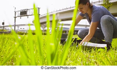 Woman ecologist getting samples of plants near highway....