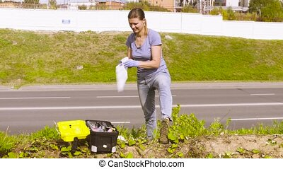 Woman ecologist getting samples of plants near highway. Then...