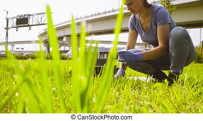 Woman ecologist getting samples of soil near highway. Damage...