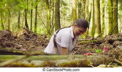 Woman ecologist in the forest digging a soil slit