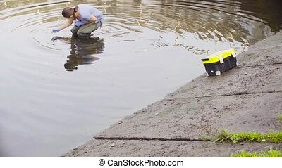 Woman ecologist measuring pH of the water in the city river....