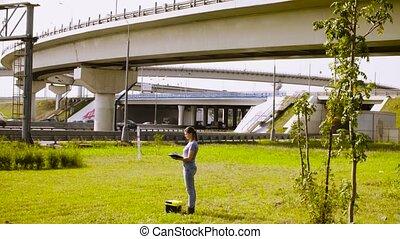 Woman ecologist writing something near highway