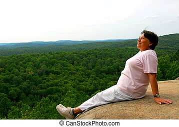 Woman edge cliff - Mature woman sitting on cliff edge...