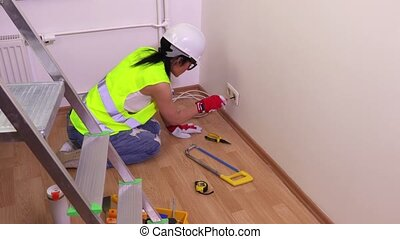 Woman electric with screwdriver near wall