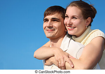woman embraces  man from behind