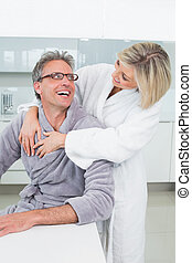 Woman embracing a man from behind in kitchen